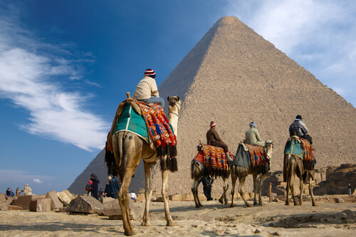 Riding camels in front of pyramids