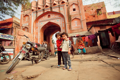 Indian kids in front of pink gate