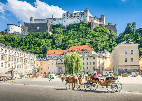 The historic city of Salzburg with traditonal horse-drawn Fiaker carriage and famous Hohensalzburg Fortress in Salzburg Austria