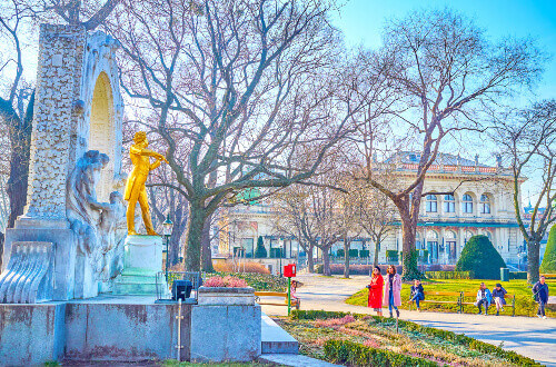 Group of tourists making selfies and photos with the Golden Strauss statue in City park in Vienna Austria