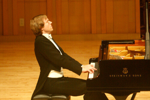 Professor Jan Jiracek von Arnim playing on a piano stage