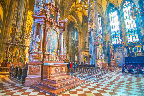 The icons in prayer hall of St. Stephens Cathedral are framed in stone kiots with carved sculptures in Vienna Austria