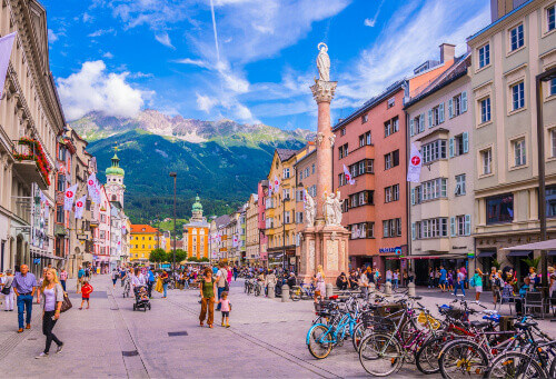 Locals and tourists passing through the town square dominated by St. Annas column in Innsbruck, Austria