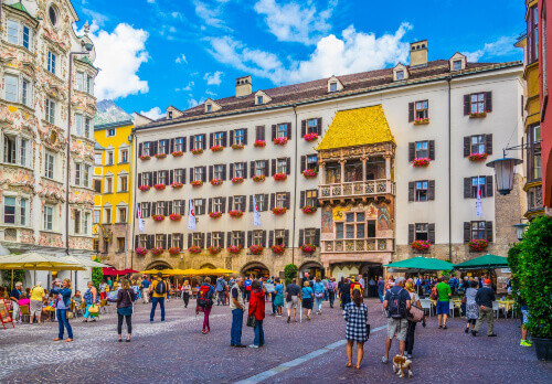 People admiring the famous Goldenes Dachl next to the Helblinghaus in Innsbruck, Austria
