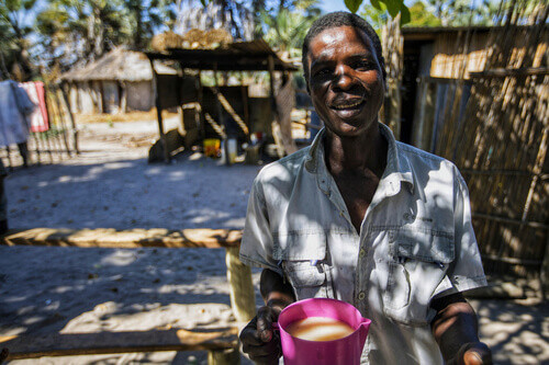 Local man holding a cup of home made beer at the front of his hut near okavango delta in Maun Botswana