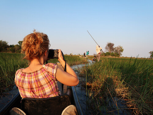 Tourist relaxing and taking pictures at traditional mokoro boat trip during sunset at Okavango Delta in  Botswana