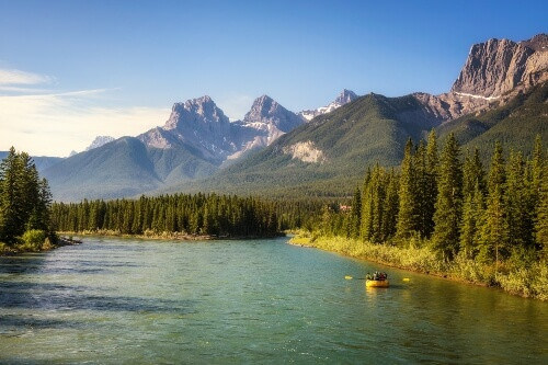 Rafting on the Bow River in Banff National Park near Canmore with the canadian rockies in the background in Alberta, Canada