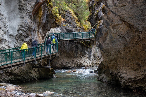 Tourists at the Johnston Canyon Lower Falls, promoting the Banff & Lake Louise Tourism in Alberta, Canada