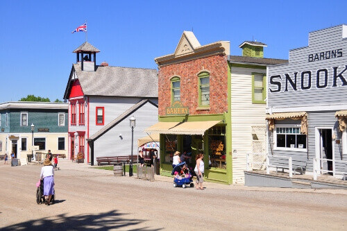 Tourists walking along Calgarys western themed living museum called Heritage Park in Alberta Canada