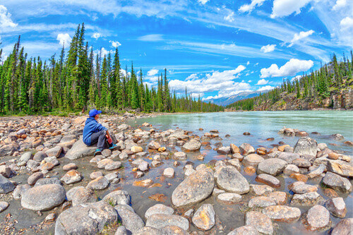 A boy sits on the edge of the Athabasca River enjoying the beautiful scenery of the Canadian Rockies in Jasper Canada