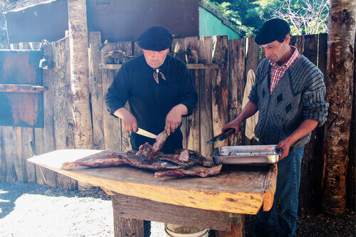 A Chilean gaucho and his assistant demonstrate the carving of a whole barbecued lamb outdoors at a ranch in Patagonia Chile