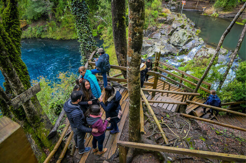 Outdoor view of tourists walking close to the waterfalls in Pucon Chile