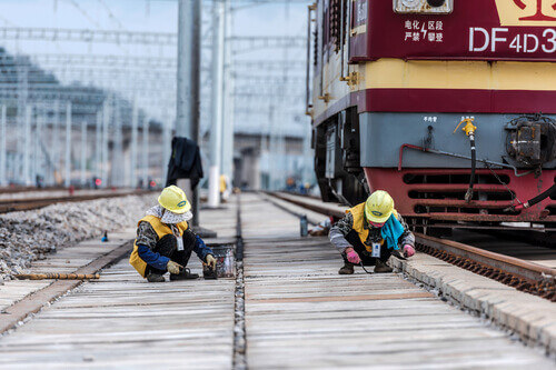 Railway workers maintain high-speed railway tracks at a high-speed railway station in Kunming China