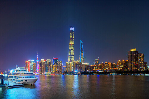 View of Skyscrapers that lit the night sky with a boat on Huangpu River in Shanghai China