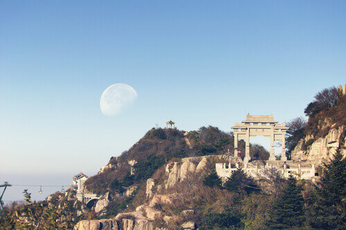 A waning moon over the mountains of Tai Shan (Mount Tai) and Peng Yuan Gate in Shandong province China