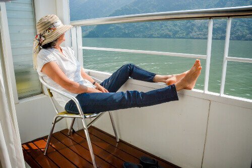 A tourist with her feet up on the railing of a cruise and enjoying the scenery in Yangtze river China