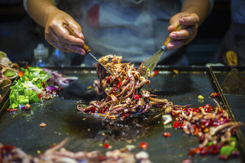 Chinese Chef making spicy squid recipe in the old town of Lijiang in the Yunnan Province in China