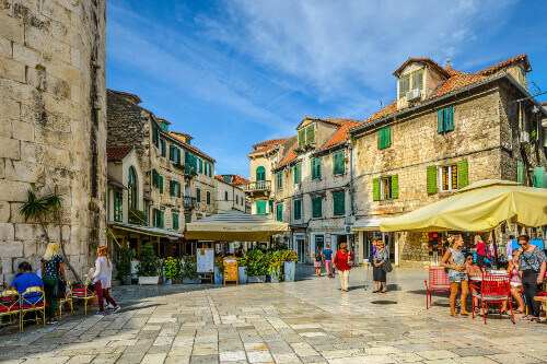Tourists enjoy cafes and shops on an early autumn afternoon on the Fruit Square in the Diocletians Palace section of Old Town Split Croatia