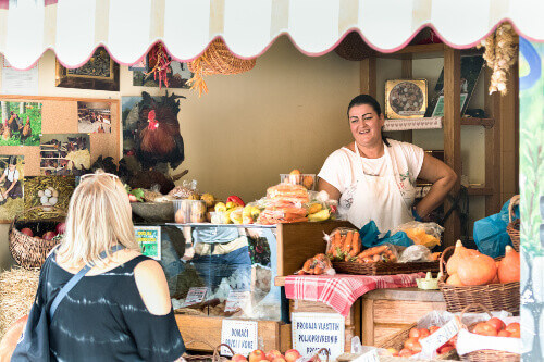 A friendly seller speaking and smiling to a customer at her grocery store in a public market in Split, Croatia
