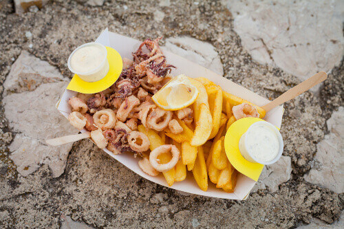 Deep fried squid with chips and white mayo sauce, traditional seaside fast food during holidays in Krk Croatia