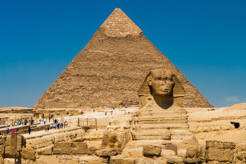 The great statue of Sphinx, a creature with a lions body and a human head and the Great Pyramid of Giza in Cairo Egypt