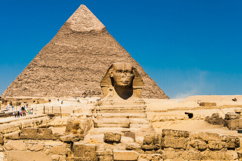 The ancient Egyptian sculpture of the great sphinx in the background of the pyramids in Giza Egypt