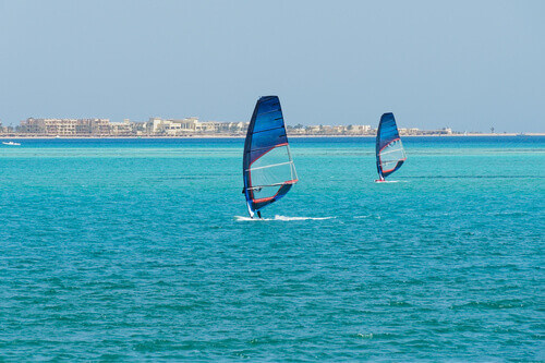 Two windsurfers crossing right to left with waterfront buildings in the far distance in Hurghada Egypt