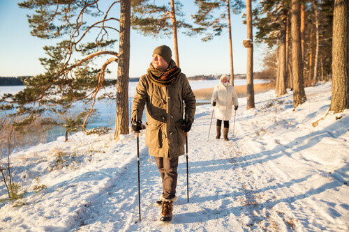 Active outdoor loving Man and Woman walking in a snowy forested area in Finland
