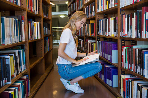 Young girl sitting in library at bookshelves searching for books in Helsinki Finland