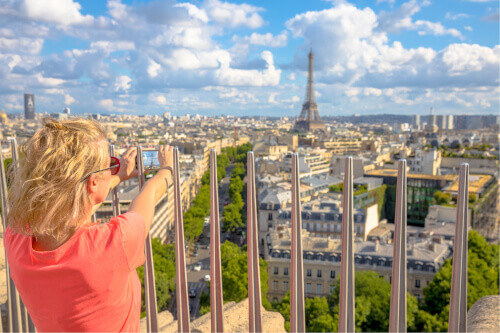 Tourist taking picture with smartphone from top of Arc de Triomphe in Paris France