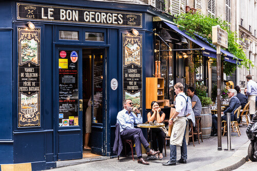 Parisians and tourists enjoy food and drinks at the street french cafe in Paris France