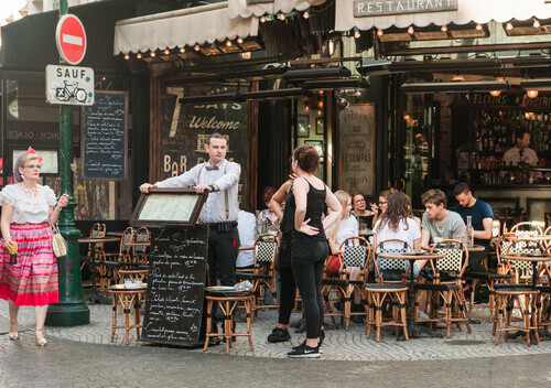 Tourist taking a waiter at a cafe in Paris France