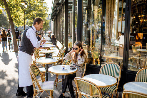 Waiter serving coffee to a young woman sitting at the traditional french cafe in Paris