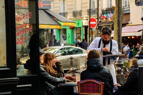 Waiter serving customers at traditional outdoor Parisian cafe on rue Mouffetard in Paris France