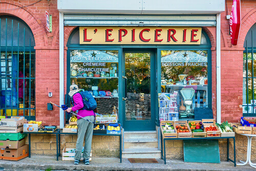 An overhead sign saying Grocery Shop with tourist shopping for fresh produce in Gigondas France