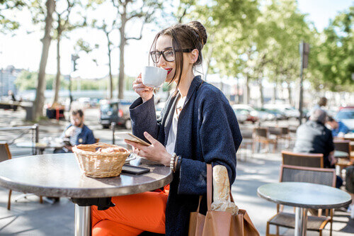 Young woman having a breakfast with coffee and croissant sitting outdoors at the french cafe in Lyon city in France