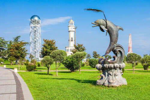 Dolpin statue and the Alphabet tower in the background in Batumi Georgia