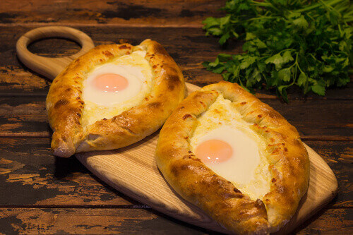 Georgian national dish called Khachapuri. A Batumi style open pastry with white cheese top with egg yolk and butter