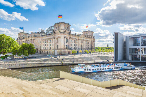 Government district with excursion boat on Spree river passing famous Reichstag building and Paul Lobe Haus in Berlin Germany
