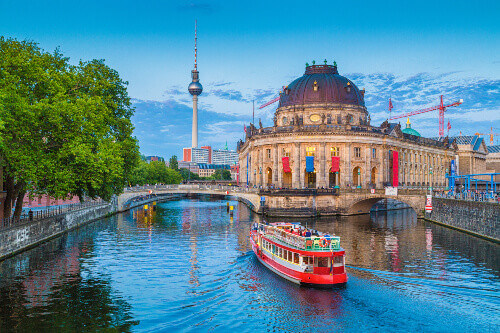 UNESCO World Heritage Site Museumsinsel (Museum Island) with excursion boat on Spree river and famous TV tower in Berlin Germany