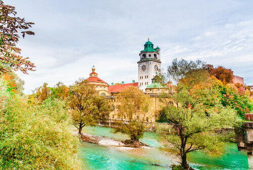 Autumn view of Isar river with the neo-baroque Muellersches Volksbad in Munich Germany