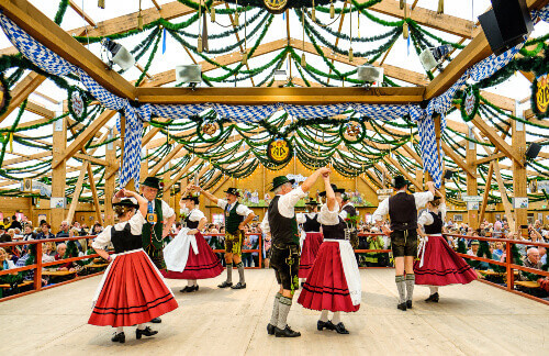 Locals in their traditional clothing at a beer tent in the biggest folk festival in the world, Oktoberfest in Munich Germany