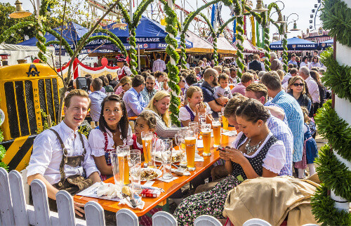 People dressed in traditional costumes sitting in the beergarden during the oktoberfest celebration in Munich Germany