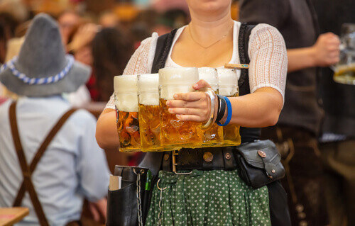 Waitress with traditional costume professionally holding beers during Oktoberfest in Munich Germany