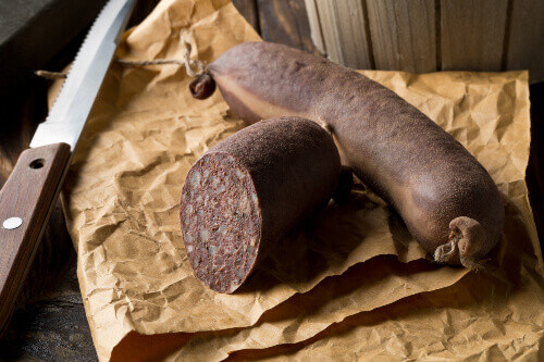 German specialty blood sausage (Blutwurst) on wooden table in kitchen