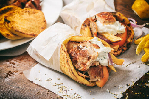 Greek gyros souvlaki wrapped in a pita bread on a wooden background