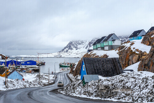 Acrtic road to the docks and port between the rocks with Inuit houses in Sisimiut, Greenland