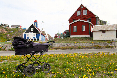 Baby carriage in front of the old church and Sisimiut Museum in Sisimiut, Greenland