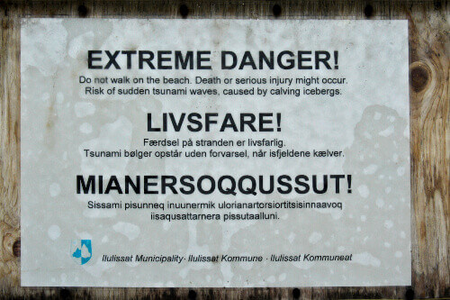 A sign on the boardwalk at Ilulissats icefjord warns of the dangers caused by calving icebergs in Ilulissat Greenland