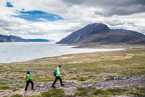 Two tourist wearing winter clothes walking in the cold vastness of Greenland